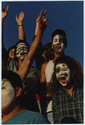 4 personas alrededor tienen sus caras pintadas de blanco y verde. Sus brazos están levantados en el aire.