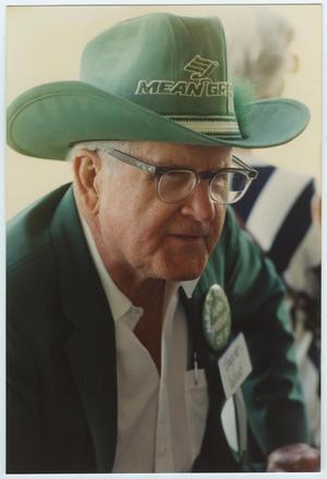 Un anciano con lentes y un sombrero verde con las palabras Mean Green en él y un símbolo de águila. El hombre también lleva un traje verde.