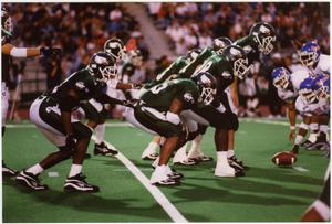 7 football players are hunched over in formation facing the right to the opposite team. The football is on the ground in between them.