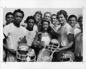 Primary view of object titled '[Miss Texas Poses with NT Football Players]'.