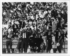 Varios jugadores de fútbol americano se sitúan en la banda con un hombre con traje. El multitud en las gradas se ve en el fondo.