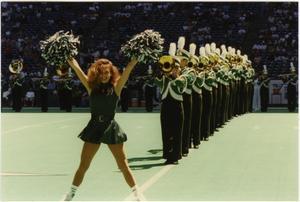 Una animadora tiene ambos brazos en el aire con pompones en ambas manos. Ella está con las piernas separadas y de pie frente a una fila de personas con  uniforme de la banda tocando instrumentos.