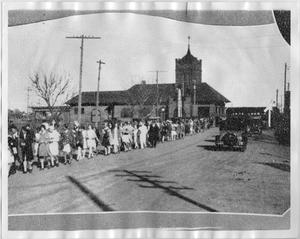 Black and white picture of a long line of people on the left side standing  in front of a church building. On the right side is a road with a black  car driving by.