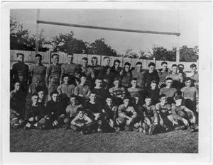 Black and white photograph of 36 men in 3 long rows. All men are in uniform  and appear to be standing in front of the field goal.