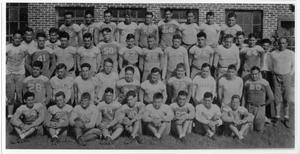 Black and white photograph of an entire football team of 45 men in rows of 4, all posing on grass in front of a brick building.