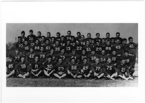 Old photograph of an entire football team in 5 rows. All are in black uniform with numbers on the front.