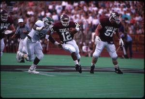 Picture in color. Eagle football player is seen close to a Texas A&M player, attempting a tackle. Another Texas A&M player is to their side on the right.
