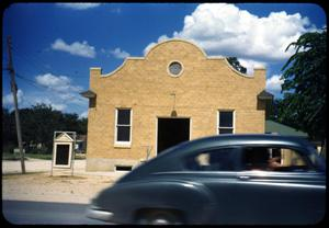 Primary view of object titled '[Photograph of Automobile Passing a Building]'.