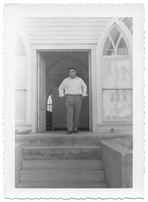 Primary view of object titled '[Man Posing in the Doorway of a Church]'.