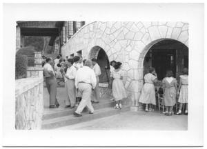 Primary view of object titled '[Church Attendees Gathering for Lunch Under Stone Arches]'.