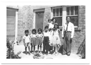 Primary view of object titled '[Hispanic Family in Front of a Brick Building]'.