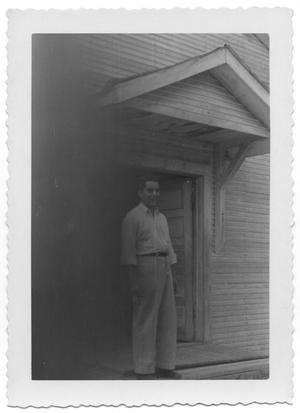 Primary view of object titled '[Man Standing Underneath the Awning of a Wooden House]'.