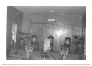 Primary view of object titled '[Three Carved Chairs and Potted Plants on a Stage]'.