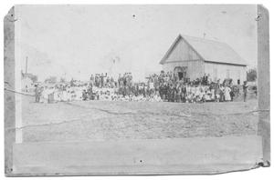 Primary view of object titled '[Large Formal Group Portrait in Front of a Large Wood Building]'.