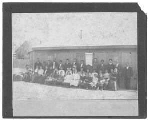 Primary view of object titled '[Group Portrait in Front of a Small Wood-Slatted Building]'.