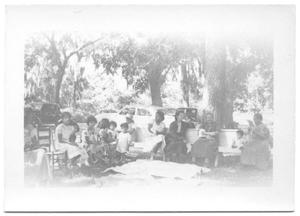 Primary view of object titled '[Women and Children Seated Outside on Benches and Chairs]'.