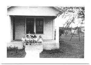 Primary view of object titled '[Seven Toddlers Sitting on a Porch]'.