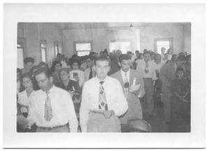 [Front View of a Large Congregation Standing in Church Pews]