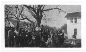 Primary view of object titled '[Group of Hispanic People Crowded Under a Crooked Tree]'.
