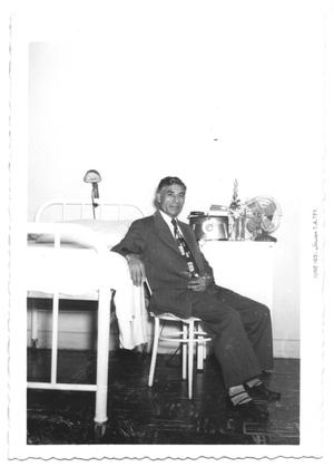 Primary view of object titled '[Reverend Seated Next to a Hospital Bed]'.