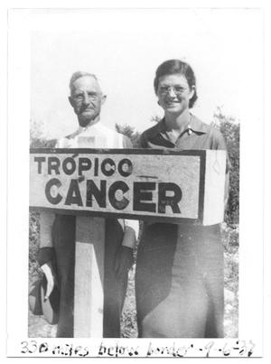 Primary view of object titled '[Couple Standing with a Tropico Cancer Sign]'.