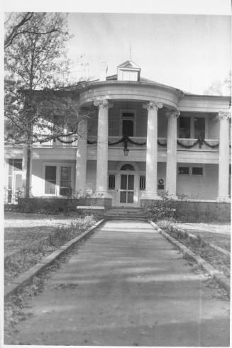 [Moore Home, Candlelight tour. View from directly in front of house.], Photograph of Moore Home, Candlelight tour. Taken as publicity shot for Saburbia newspaper. Photograph was taken from the center sidewalk that leads to the front entrance. Balcony rail has garland across the length of it. Tall tree on left of photograph. Photograph has large blank area at top and is tilted to right on paper.,