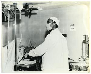Primary view of object titled '[Dr. Herman A. Barnett Works on a Patient Before Surgery]'.
