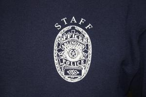 Primary view of object titled '[Image of an imprinted APD badge on a shirt]'.