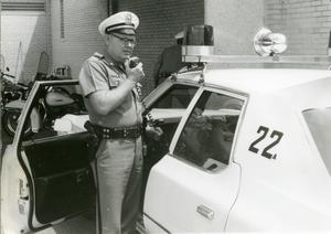 Primary view of object titled '[Arlington Police Officer Bill Taylor speaking over mobile radio, ca. 1965, view 1]'.