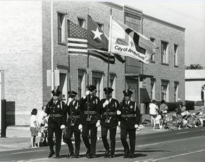 Primary view of object titled '[APD Color Guard marching in the Arlington Fourth of July Parade, late 1980s]'.