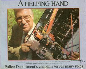 Primary view of object titled '[Arlington Police Chaplain Harold Elliott holding a photograph taken at the bombed Alfred P. Murrah Federal Building (newspaper clipping, 1996)]'.