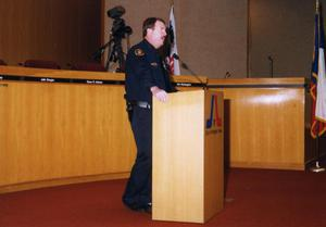 Primary view of object titled '[Arlington Police Officer Dee Anderson speaking in city council chamber room]'.