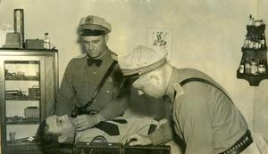 Primary view of object titled '[Texas State Highway Patrolmen testing first breathalizer on Chief Cribbs, view 1]'.