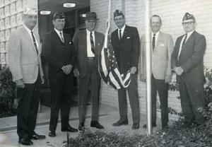 "Primary view of object titled '[Arlington Police Chief A.B. ""Ott"" Cribbs with VFW members raising a U.S. Flag at the opening of the Main St. Police Station]'."