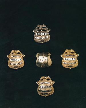 Primary view of object titled '[APD badges, earlier versions, 1st close view]'.