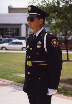 Primary view of object titled '[APD Honor Guard officer, Gary Krohn, standing at attention]'.