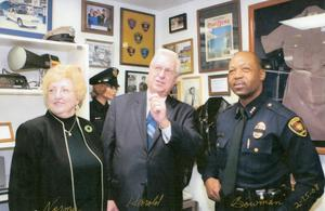 Primary view of object titled '[APD Chaplain Elliott, his wife, and Chief Bowman at the grand reopening of the museum at the Arlington Training Center]'.