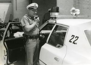 [Arlington Police Officer Bill Taylor speaking over mobile radio, ca. 1965, view 2]