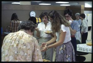 Primary view of object titled '[People Congregate at a Table of Food in Austin Public Library Staff Room]'.
