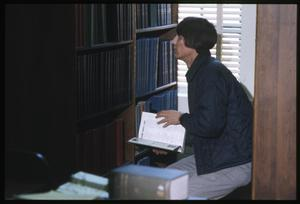 Primary view of object titled '[Man Looks Through a Bookshelf at the Dr. Eugene Clark Public Library]'.