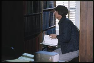 [Man Looks Through a Bookshelf at the Dr. Eugene Clark Public Library]