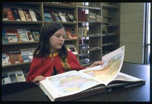 Primary view of object titled '[Young Girl Flips Through an Atlas]'.