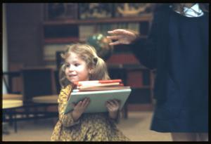 Primary view of object titled '[Young Girl Carries Stack of Books]'.