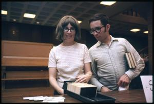 Primary view of object titled '[Man and Woman Look Through Card Catalog]'.