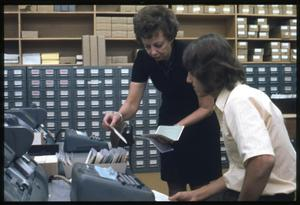 Primary view of object titled '[Librarian Virginia Kuse Helps Man Look Through Card Catalog in an Office Space]'.