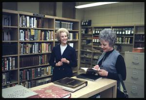 Primary view of object titled '[Two Women Speak in the Literature Section of a Library]'.
