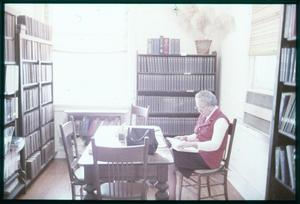 Primary view of object titled '[Woman Sits in a Library Room]'.