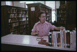 Primary view of object titled '[Librarian at Book Return Counter]'.