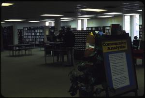 Primary view of object titled '[Library Interior with Community Analysis Sign]'.