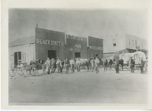 Primary view of object titled '[Blacksmith shop with buggy out front]'.